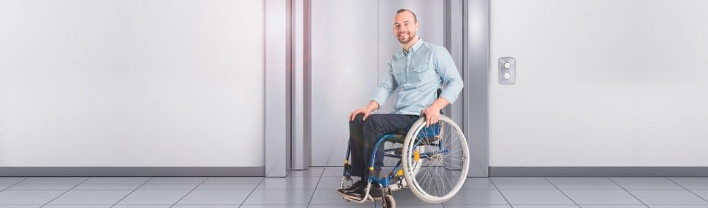 Homem cadeirante esperando por elevador residencial para deficientes